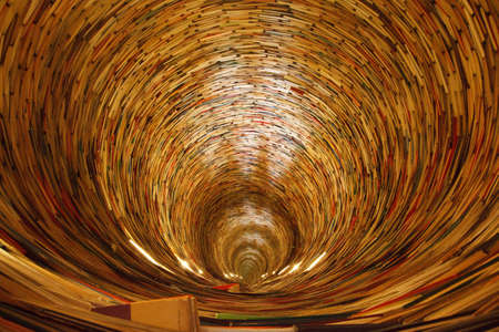 a book tunnel in Pragues library. Yes, mirrors are used to create this effect. Stock Photo