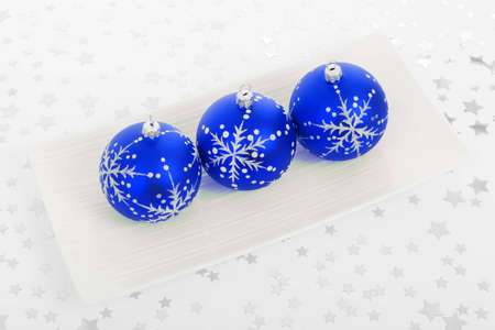 three blue baubles on the plate with stars on the background Stock Photo