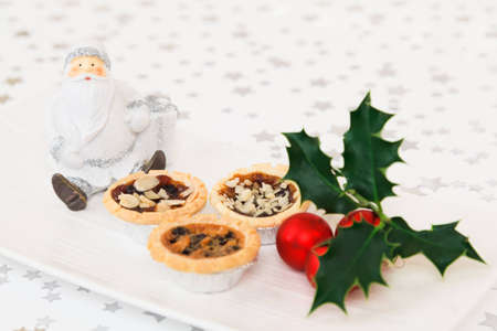 Santa Claus decoration with mince pies and holly on plate with starry background