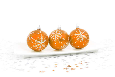 orange baubles on a plate with stars on the background