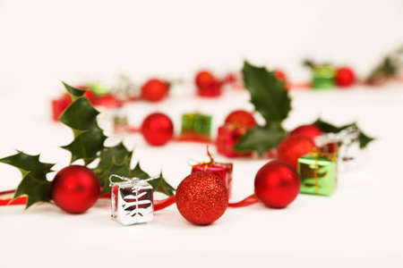a curve shape created with baubles. presents and holly on white background Stock Photo