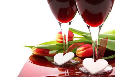 valentine decoration with two glasses of wine, white hearts and colorful tulips on white background Stock Photo - 9117393