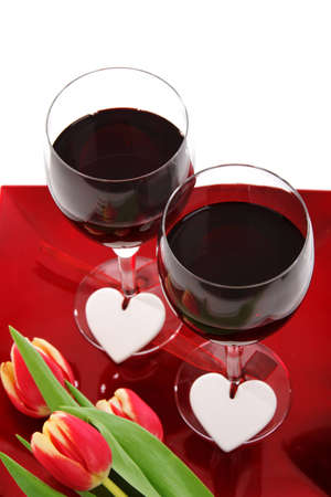 two glasses of wine with heart decoration and tulips on white background Stock Photo - 9117638