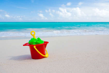 colorful bucket and other sand toys on beach with the sea in the background Stock Photo