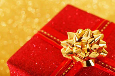 Red Christmas present on a blurred golden background