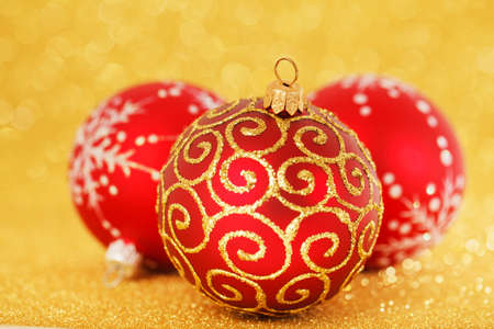 three red christmas balls on a golden background
