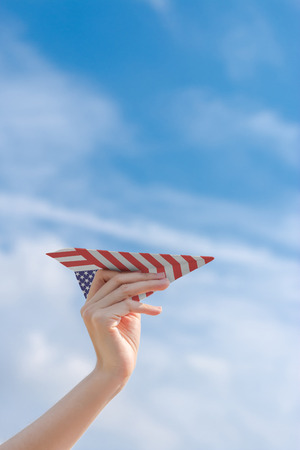 Hand holding paper American flag plane with blue sky Stock Photo