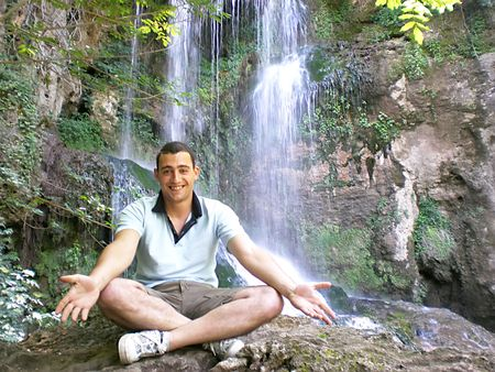 young man meditating in front of waterfall photo