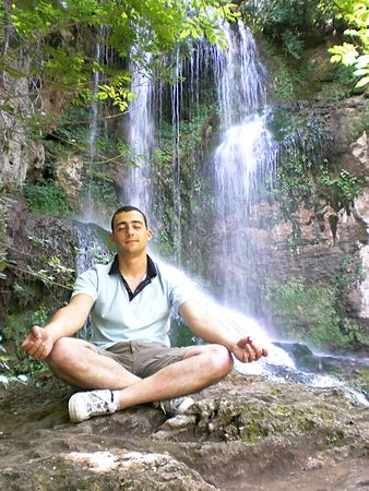 lithe: young man meditating in front of waterfall  Stock Photo