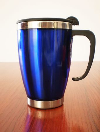 travel mug: Stainless steel travel mug on a wooden table