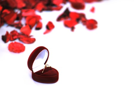 engagement ring in red box and petals on white background photo