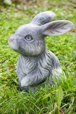 kaolin: rabbit statue on green grass backgound Stock Photo