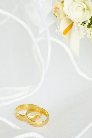 wedding rings and flowers decorations over bridal veil