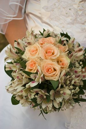 wedding bouquet with roses in brides hands photo