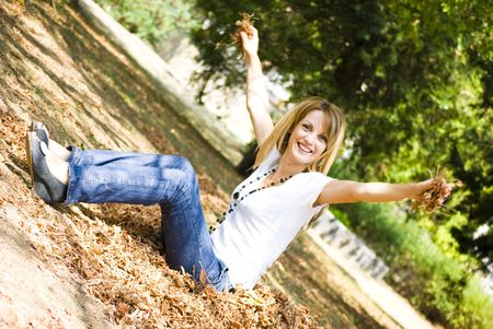 beautiful young model throwing leaves in park photo