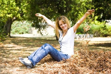 beautiful young model throwing leaves in park Stock Photo - 5412801