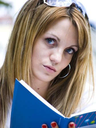 beautiful young woman reading book outdoor photo