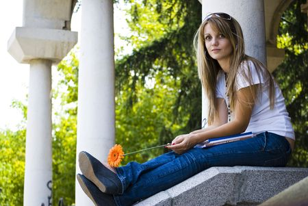 beautiful young woman with books and flower outdoor photo