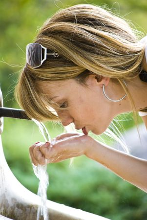 young woman drinking water in park photo