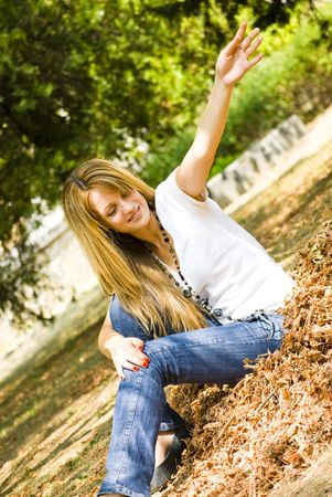 beautiful young model throwing leaves in park Stock Photo - 5489742