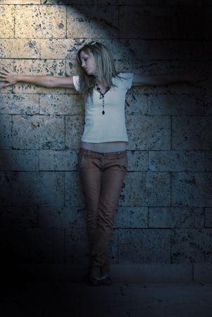 beautiful young model posing on wall photo