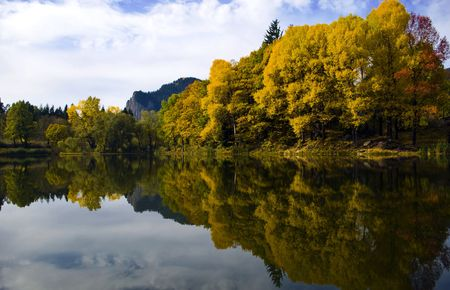 colorful autumn trees reflected on a lake in Bulgaria photo