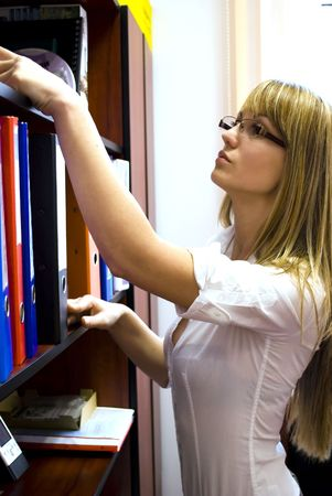 young and sexy secretary searching for documents photo