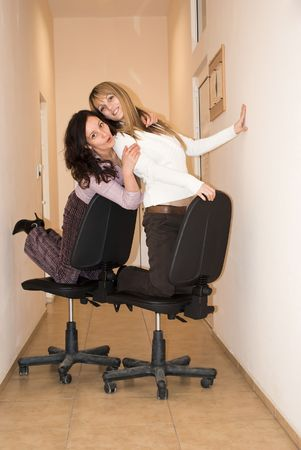 two colleagues making fun with chairs photo