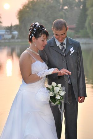 groom and bride on sunset near lake looking at their wedding rings photo