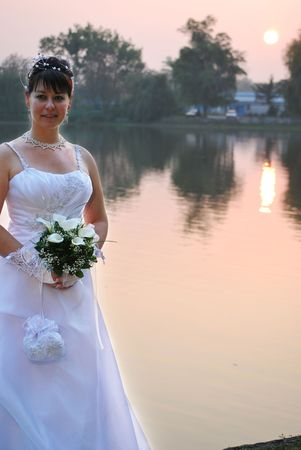 bride holding her bouquet on a lake in sunset photo