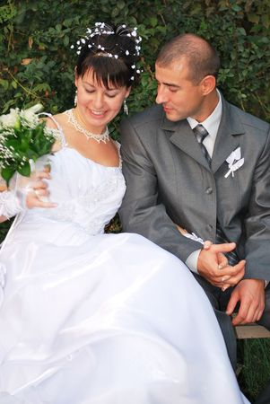 lovely bride and groom portrait on a bench photo