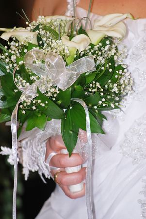 bride holding wedding bouquet in her arms photo