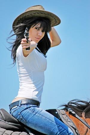 point and shoot: preciosa ni�a sosteniendo una pistola y montando a caballo