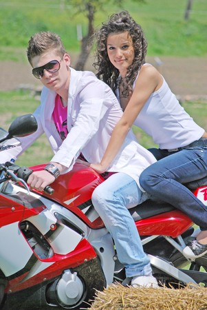 young couple in love riding a motorbike Stock Photo - 7034606
