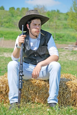 young cowboy holding a gun sitting on a hay bale photo