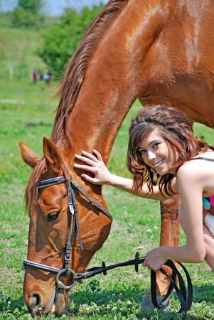 barn girls: young and attractive woman riding brown horse