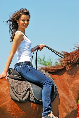rodeo cowgirl: young and attractive woman riding brown horse