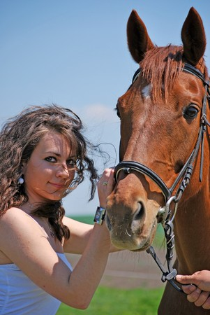 young and attractive woman riding brown horse photo