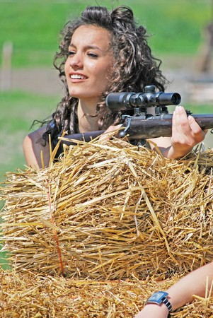 point and shoot: ni�as con el arma en un fardo de heno Foto de archivo