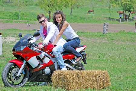 young couple in love riding a motorbike photo