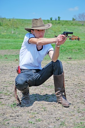 young teenager with cowboy hat holding a gun photo