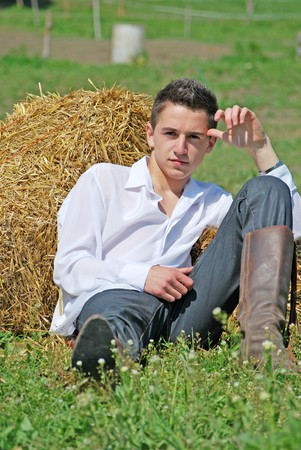 young attractive man posing on hay bale Stock Photo - 7140890