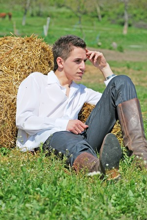 young attractive man posing on hay bale photo
