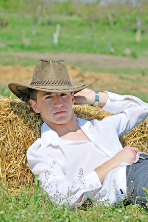 working cowboy: young attractive man posing on hay bale