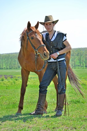 young and attractive man riding brown horse Stok Fotoğraf