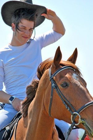 young and attractive man riding brown horse Stock Photo