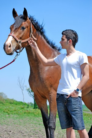 young and attractive man riding brown horse photo