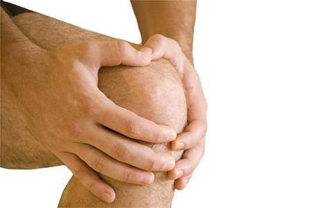 anatomy knee: man having pain in his knee making massage Stock Photo