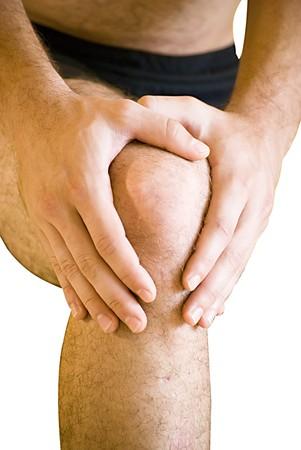 man having pain in his knee making massage photo