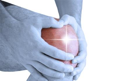 sports injury: man having pain in his knee making massage Stock Photo